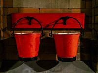 Vintage fire buckets hanging on hooks attached to brick wall.