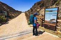 Hiker and interpretive sign at Bechers Bay, Santa Rosa Island, Channel Islands National Park, California USA.