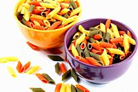 Colored macaroni in orange and purple bowl with white background