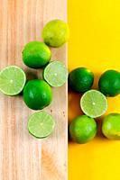Limes on wooden board with yellow background