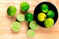 Limes in black bowl on wooden board