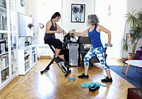 Mother and daughter doing sports in the living room of their house in Madrid (Spain)