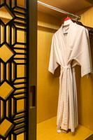 white bathrobe with wooden hangers in wardrobe.
