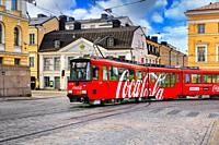 Moving HSL tram with Coca-Cola advertising and Sederholm House, the oldest building in inner city, in the background. Helsinki, Finland. May 25, 2020.