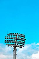 Retractable floodlight against clouds and blue sky - vertical view.