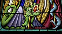 The dragon on a stained glass window in the Chapel of the 7 Saints in Erdheven. Morbihan, Brittany, France.