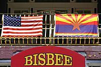 American flag alongside a rainbow Arizona State flag on a balcony in Bisbee, AZ.
