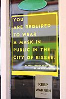 """Sign in a store window in Bisbee AZ - """"""""You are required to wear a mask in public in the city of Bisbee""""""""."""