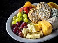 Fruit cheese and crackers and a plate on a black background.