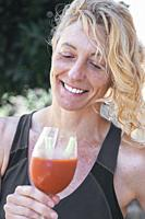 Young mature blonde woman in sportswear outdoor with a glass of tomato juice.