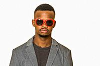 Confident African American guy in jacket and trendy sunglasses looking at camera against gray background.
