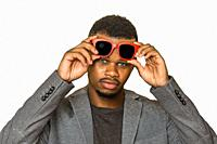 Confident black man in smart casual outfit lifting stylish sunglasses and looking at camera against gray background.