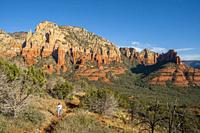 View of the landscape of Ship Rock and Steamboat Rock from the Brins Mesa Trail with a hiker (model released) near Sedona, Arizona, USA.