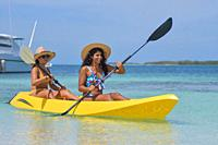 Two young Hispanic women paddling in yellow kayak at summer travel destination. Exotic Caribbean beach with turquoise water sea.