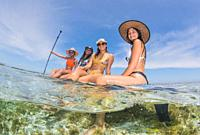 Group of mixed ethnicity young women on Paddle board enjoying friendship at summer travel to Caribbean beach with turquoise water sea.