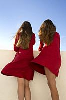 Two young girls with red dresses and long blonde hair at the wind.