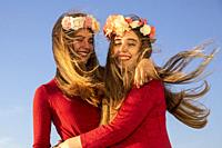 Two young girls with red dress and long blonde hair at the wind and roses having fun.