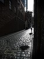 A man walks down a deserted, dark alley reading his newspaper.