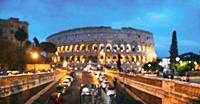 Rome, Italy. Colosseum Also Known As Flavian Amphitheatre. Traffic In Rome Near Famous World Landmark In Evening Time. Abstract Blurred Background. Bl...