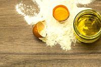 Flour, egg and oil on a table.
