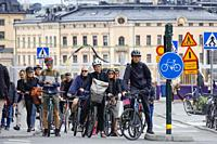 Stockholm, Sweden Commuters with bicycles stopped at a red light at Slussen.