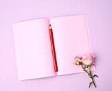 open notebook with pink sheets and pink rose on a purple background, flat lay.