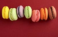 pile of multi-colored baked macarons almond flour cakes on a red background, copy space.