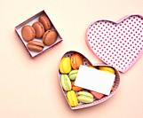round baked multicolored macarons lie in a pink cardboard box in the shape of a heart on a beige background, top view.
