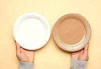brown and white paper disposable plates on a beige background, top view. The concept of rejection of plastic, environmental conservation.