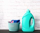 plastic round laundry basket and green bottle with liquid laundry powder on white brick wall background.