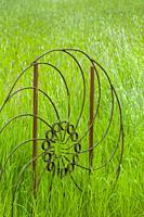 An old metal wheel in a field of grass at the Dahmen Barn (Art Barn) in Whitman County in the Palouse near Pullman, Eastern Washington State, USA.