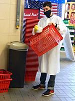 Supermarket Worker Cleaning Handle Baskets, Wellsville, New York, USA.