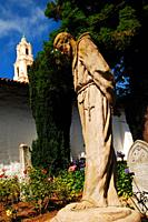 A statue of Junipero Serra stands solemnly in the courtyard of Mission Dolores in San Francisco.