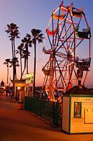 A Ferris wheel is illuminated at dusk at the Balboa Fun Zone in Newport Beach, California.