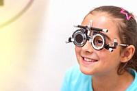 Try-on tool for vision check for the young girl patient in front of the eye chart in the cabinet. Eye doctor with patient in the clinic. Ophthalmologi...