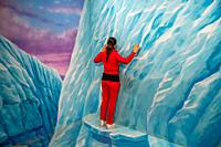 Back view of a woman climbing ice wall.