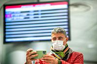 Man wearing face mask at the airport in front of departure board.