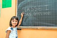 Young girl on her first day of elementary school in the classroom writing on the chalkboard.