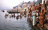 Varanasi, Uttar Pradesh, India, Asia - Religious pilgrims bathe and pray at a ghat of the holy Ganges River. Varanasi (Benares) is one of the oldest c...