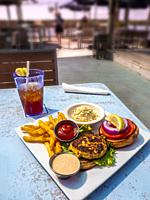 Lunch plate of Crab Cake sandwich french fries cole slaw and Iced Tea on light blue table at waterfront restaurant in Florida.