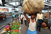 Kolkata (Calcutta), West Bengal, India, Asia - A coolie along with other people walk past a street market at one end of the Howrah Bridge with daily t...