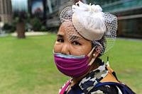 Singapore, Republic of Singapore, Asia - Portrait of a woman who covers her face with a protective face mask to protect herself and others against an ...