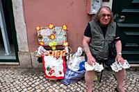 Lissabon, Portugal, Europe - An old man sits at the roadside in front of a building in the old part of town of the Portuguese capital city and sells f...