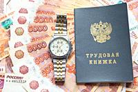 On a pack of five thousandth bills there is a work book and a watch.
