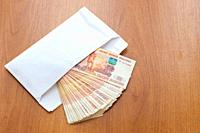 There is a bundle of money in an envelope on the table.