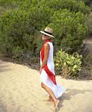 Mature woman in a white suit enjoying an afternoon on the Islantilla beach, Huelva