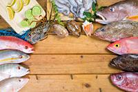 Caribbean Fresh fish seafood on old wooden table. Top view. Close-up.