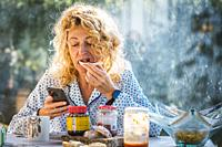 Blonde young mature woman in pyjamas at home in breakfast time looking his mobile and eating a toast.
