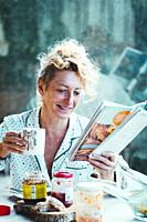 Blonde young mature woman in pyjamas at home in breakfast time, reading a magazine and having a cup of coffee.
