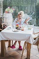 Blonde young mature woman in pyjamas at home in breakfast time, reading a magazine and eating a toast.